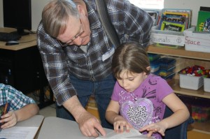 Garland Master Bill Bemis helps a third grader. (Photo by Walter Boomsma)