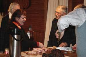 State Overseer Vicky Huff is joined by Nancy and Guy Ellms at the ham carving station.