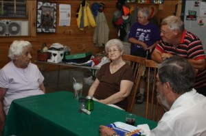 Dot., Betty, Bill, and Jim share a moment while Mary (rear) checks out the auction table.