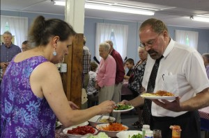 Erin Callaway, Master of East Sangerville Grange serves Mike Griffin a super salad.