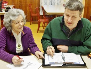 Treasurer Bonnie Goodenow goes over plans for the flea market and Grange Month supper with Master Craig Johnson