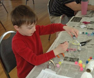 William works on painting the birdfeeder he made from a soda bottle.