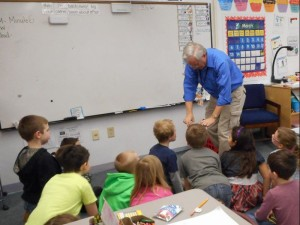 Second graders watch and listen for the magic moment when butter appears in the jar.